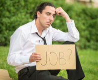 Unemployed man. Frustrated unemployed man with sign sitting at the lawn Stock Image