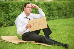 Unemployed man. Frustrated unemployed man with sign sitting at the lawn. Depression Royalty Free Stock Images