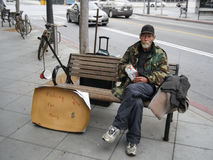 Unemployed man sitting on a bench and begging for money. Los Angeles, CA, United States - 16 June 2010. Unemployed man sitting on a bench and begging for money Royalty Free Stock Photography