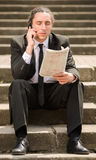 Unemployed man. Man in suit sitting at stairs with newspaper. Unemployed man looking for job stock photo
