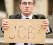 Unemployed man. Man in suit sitting at stairs with sign in hands. Unemployed man looking for job Royalty Free Stock Images