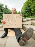 Unemployed man. Man in suit sitting at stairs with sign. Unemployed man looking for job Royalty Free Stock Photo