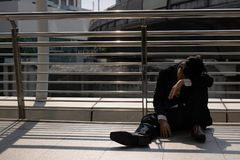 Unemployed stressed young Asian business man sitting on floor outdoors. Failure and layoff concept.  stock photography