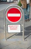 Unemployed ?. Text `unemployed ? start your own business` in bold red letters on a stop or no entry sign, street scene behind stock photography