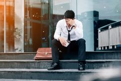 Unemployed tired or stressed businessman sitting on the walkway. After work stressed businessman concept Stock Image