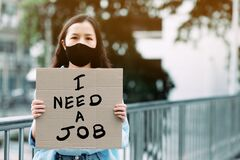 An unemployed women holding a paper sign writing a message saying she needs a job