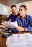 Unemployed young couple with debts reviewing their Royalty Free Stock Photo