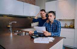 Unemployed young couple with debts reviewing their Stock Photos