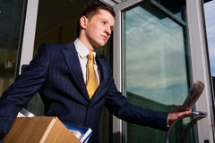 Unemployed young manager leaving business center. Financial crisis. Unemployed young manager leaving business center in megalopolis Stock Images