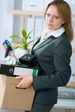 Unemployment concept. A fired woman in a suit carrying a box of personal items Stock Photos