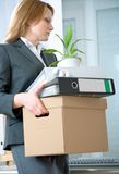 Unemployment concept. A fired woman in a suit carrying a box of personal items Royalty Free Stock Photos