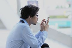 Unemployment concept. Side view of unemployed young Asian man looking mobile smart phone at outside city background. Unemployment concept. Side view of stock image