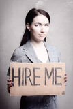 Unemployment. Young girl holds a cardboard sign. Hire Me Stock Photo