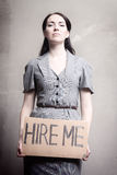 Unemployment. Young girl holds a cardboard sign. Hire Me Stock Photos