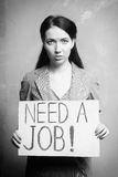 Unemployment. Young girl holds a cardboard sign. Need a Job. black and white Stock Photo