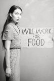 Unemployment. Young girl holds a cardboard sign. Will Work for Food. black and white Stock Photo