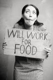 Unemployment. Young girl holds a cardboard sign. Will Work for Food. black and white Stock Image