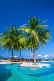 Unendlichkeitspool über tropischer Lagune mit Palmen und blauem Himmel Stockbilder