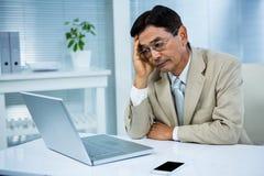 Unentschiedener Geschäftsmann schaut seinen Computer Stockfotografie
