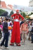 Unentschiedener roter Clown auf Stelzen Stockbilder