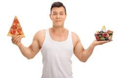 Unentschlossener Mann, der kleinen Einkaufskorb und Pizzascheibe hält Lizenzfreie Stockbilder