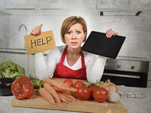 Unerfahrene Hauptkochfrau im roten Schutzblechschreien hoffnungslos und frustriert an der inländischen Küche im Druck stockbild