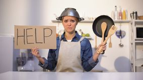Unerfahrene Hausfrau, die um Hilfe im Kochen, tragender Topf auf Kopf, Witz bittet stock footage