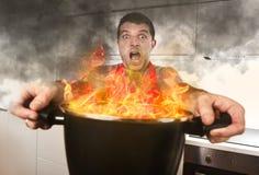 Unerfahrener Hauptkoch mit dem Schutzblech, das den Topf brennt in den Flammen mit Druckpanik-Gesichtsausdruck hält Stockfotografie