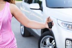 Unerkennbare Frau, die in der Hand Zündschlüssel nahe eigenem Neuwagen zeigt Stockfoto