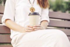 Unerkennbare Frau, die mit Mitnehmertasse kaffee sitzt lizenzfreie stockfotos