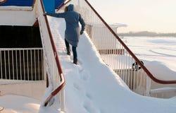 Unerkennbare Frau in einem Matrosen klettert oben ein schneebedecktes Treppenhaus Rückseitige Ansicht lizenzfreies stockfoto