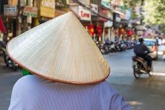 Unerkennbare Frau im traditionellen Hut in Hanoi, Vietnam stockbild