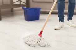 Unerkennbare Frau mit dem Mopp bereit, Boden zu säubern stockfoto