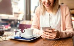 Unerkennbare Frau mit Smartphone in trinkendem Kaffee des Cafés Stockfotos