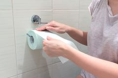 Unerkennbare Frau, sitzend auf einer Toilette und einem Rückspulen und ein Toilettenpapier auseinander reißen Konzeptbild von Ver lizenzfreie stockfotografie
