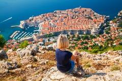 Unerkennbare Frau, welche die alte Stadt Dubrovniks betrachtet Lizenzfreie Stockbilder
