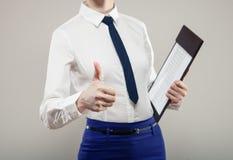 Unerkennbare Geschäftsfrau, die Dokumente verwahrt und Daumen zeigt stockbild