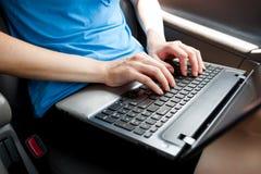 Unerkennbare Geschäftsfrau, die im Auto mit Laptop-Computer auf ihren Knien sitzt Stockfotografie