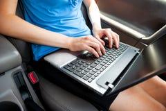 Unerkennbare Geschäftsfrau, die im Auto mit Laptop-Computer auf ihren Knien sitzt Lizenzfreie Stockfotos