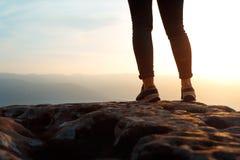 Unerkennbare junge Erfolgsfrauen-Wandererbeine auf Bergspitzefelsen, hintere Ansicht Konzept, das Ziel, Beginn des Weges erzielt, lizenzfreie stockbilder