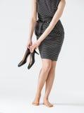Unerkennbare junge Frau, die schwarze Schuhe hält Lizenzfreies Stockfoto