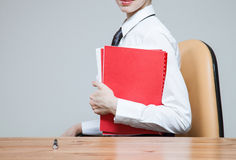 Unerkennbare junge Geschäftsfrau auf Arbeitsplatz mit Ordnern Lizenzfreie Stockfotos
