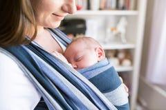 Unerkennbare junge Mutter mit ihrem Sohn im Riemen lizenzfreie stockfotografie
