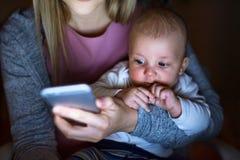 Unerkennbare Mutter mit Sohn in den Armen, Smartphone halten Lizenzfreie Stockfotos