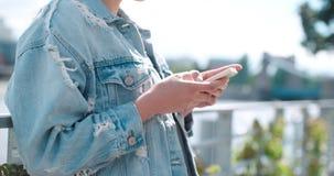 Unerkennbare tragende Denimjacke der jungen Frau, die am Telefon während des sonnigen Tages schreibt Stockbild
