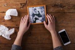 Unerkennbare traurige Frau, die gebrochenes Bild von Paaren in der Liebe hält Stockfoto