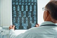 Unerkennbarer älterer Doktor überprüft MRI-Bild Lizenzfreies Stockfoto