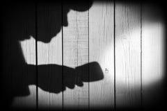 Unerkennbarer Einbrecher mit Taschenlampe im Schatten auf hölzernem backg Lizenzfreie Stockfotos