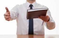 Unerkennbarer Geschäftsmann, der ein Buch gibt und ein handshak anbietet Stockfoto