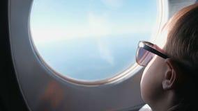 Unerkennbarer Junge schaut heraus das Fenster der Fläche in der Sonnenbrille stock video footage